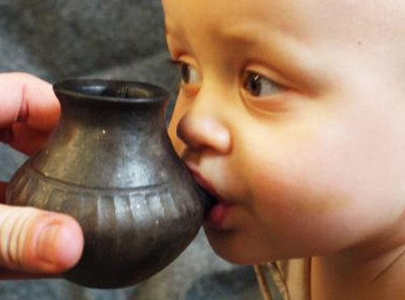 תינוק שותה מרפליקה של בקבוק חרס עתיק | Helena Seidl da Fonseca
