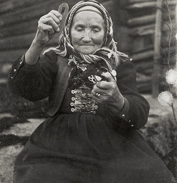 אישה שוודית מקישה כלי פלדה באבן צור כדי להדליק אש, 1916 | ויקיפדיה, Nils Keyland