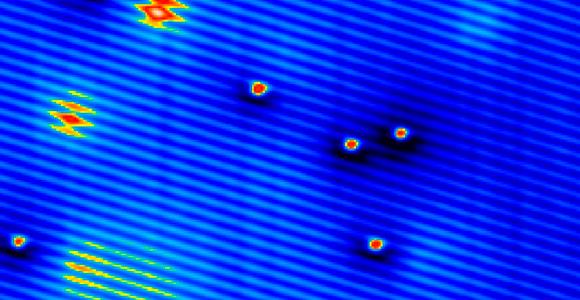 צילום (צבוע) במיקרוסקופ אלקטרונים המראה את הספינים של אטומי מנגן כענן אדום-צהוב | מקור: Science Photo Library