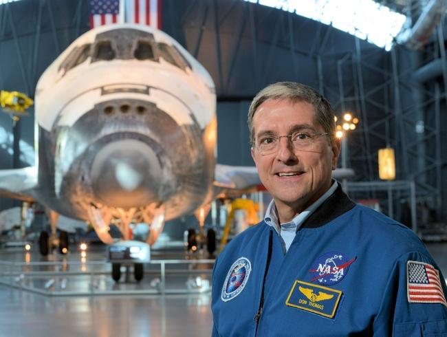 האסטרונאוט דון תומאס על רקע המעבורת דיסקברי | מקור: nssofnt