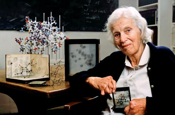 בין קריסטלוגרפיה לפוליטיקה. קרופוט-הודג'קין ב-1989 עם דגמים של כמה מהמולקולות שאת המבנה שלהן פענחה   מקור: CORBIN O'GRADY STUDIO / SCIENCE PHOTO LIBRARY