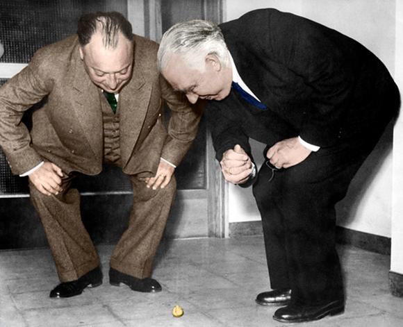 בוהר (מימין) ועמיתו וולפגנג פאולי בוחנים התהפכות של סביבון ב-1955 | PHOTOGRAPH BY ERIK GUSTAFSON WITH PERMISSION FROM THE GUSTAFSON FAMILY, COLOURED BY SCIENCE PHOTO LIBRARY, COURTESY NEILS BOHR ARCHIVE, AMERICAN INSTITUTE OF PHYSICS