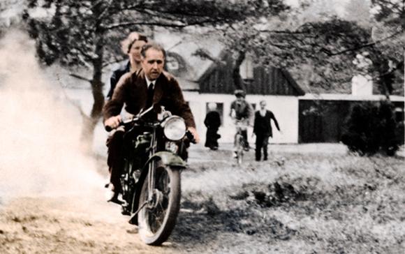 לא הבין מדוע האלקטרונים לא נופלים. בוהר ואשתו מרגריט על האופנוע של חברו, הפיזיקאי ג'ורג' גאמוב | PHOTOGRAPHER GEORGE GAMOW, COLOURED BY SCIENCE PHOTO LIBRARY FROM A MONOCHROME COURTESY OF NEILS BOHR ARCHIVE, AMERICAN INSTITUTE OF PHYSICS