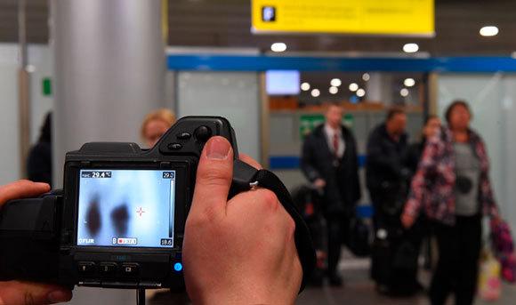 מצלמה תרמית בודקת את הטמפרטורה של נוסעים בשדה תעופה | Sputnik, SPL