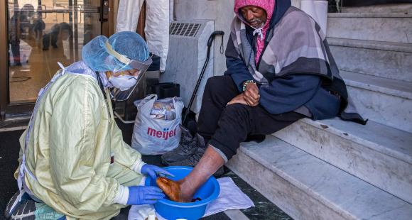 רופאה בדטרויט מטפלת בכף הרגל של חסר-בית חולה סוכרת | צילום:  JIM WEST / SCIENCE PHOTO LIBRARY