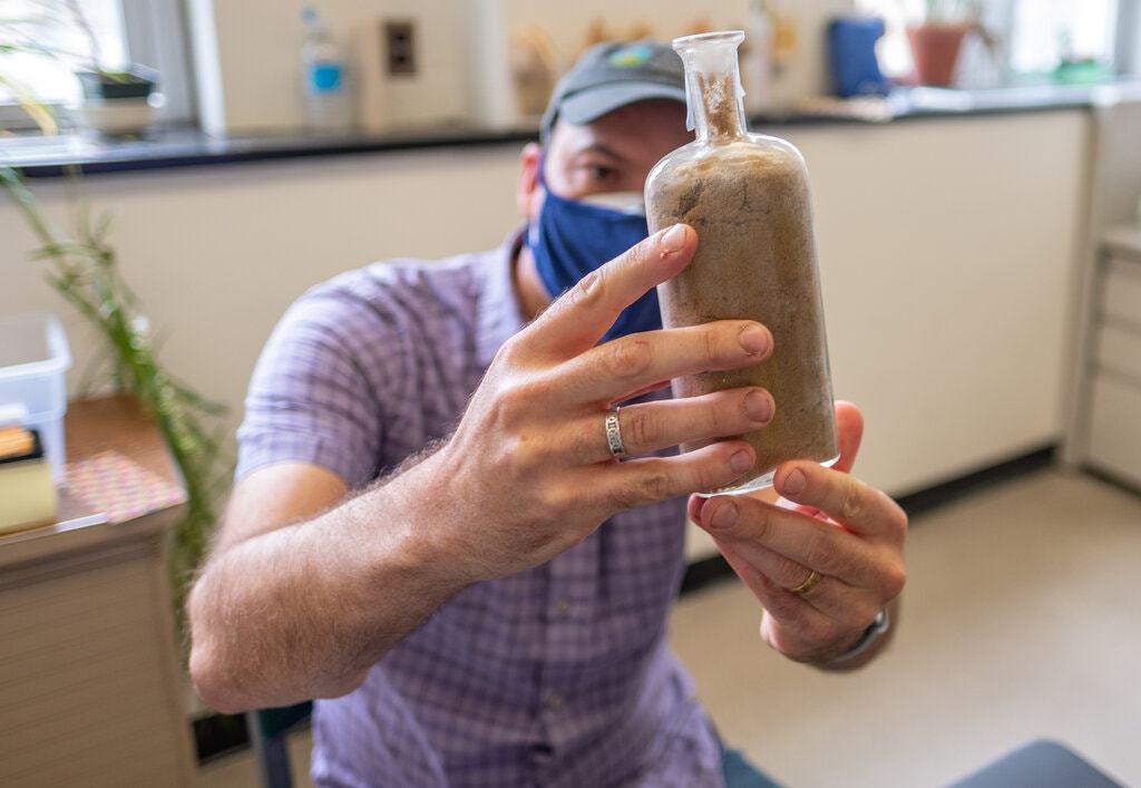 החוקר דיוויד לורי (Lowry) עם בקבוק זרעים שהוצא מהאדמה | צילום: דרק ל' טרנר, אוניברסיטת מישיגן סטייט