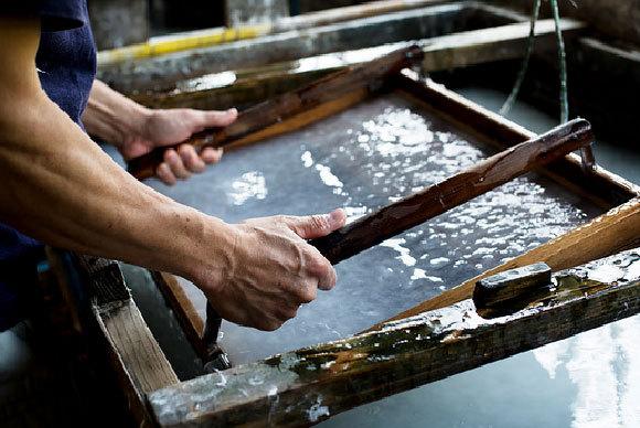 אדם מדגים הכנה מסורתית של נייר ביפן | Mint Images, Science Photo Library
