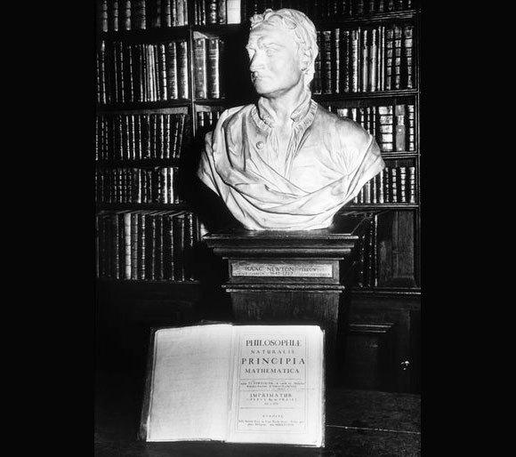 פסל בדמותו של ניוטון לצד העותק שלו של פרינקיפיה מתמטיקה, בספריית טריניטי קולג' בקיימברידג' | Simon Marsden, Science Photo Library