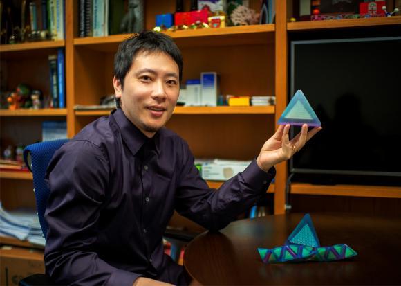 סוג חדש של גביש. ראש צוות המחקר, אוּ צֶ'ן, עם דגם של פירמידה המרכיבה את הגביש | צילום: אוניברסיטת בראון