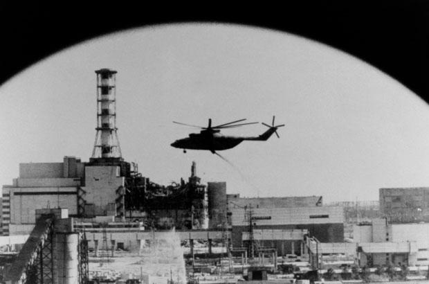 מסוק מטיל חומרים סופגי קרינה על ליבת הכור החשופה לאחר הפיצוץ | מקור: Science Photo Library