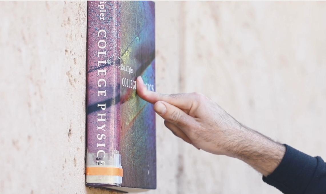ספר מוצמד לקיר באמצעות אצבע | צילום: ליאורה זייתון