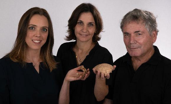 משמאל לימין: שריג, מאי והרשקוביץ, מחזיקים את שבר הגולגולת והלסת שנמצאו באתר   אילן טיילר ואבי לוין, הפקולטה לרפואה של אוניברסיטת תל-אביב