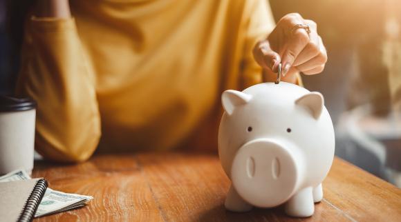 אשה משלשלת מטבע לקופת חיסכון | צילום: Nattakorn_Maneerat, Shutterstock