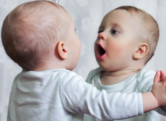 ילדים מערביים מזהים את עצמם במראה מגיל שנה וחצי - שנתיים. תינוק מתבונן בהפתעה במראה | צילום: Shutterstock