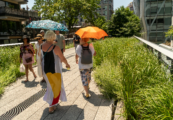 המטריות עברו לתפקד כשמשיות. תיירות מתגוננות מהשמש בניו-יורק | צילום: rblfmr, Shutterstock