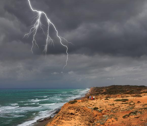 גם הקרבה לים משפיעה על האקלים המקומי, כי הוא מאדה מים שיוצרים עננים. גשם בחוף הים | צילום: Shutterstock