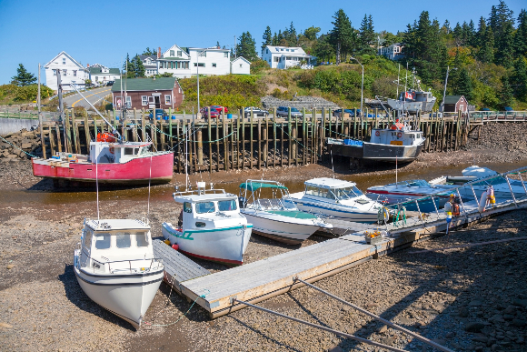 At low tide the boats rest at the bottom. A dock at the Bay of Fundy, where the difference between high and low tide is the largest in the world | Image: Noel V. Baebler, Shutterstock