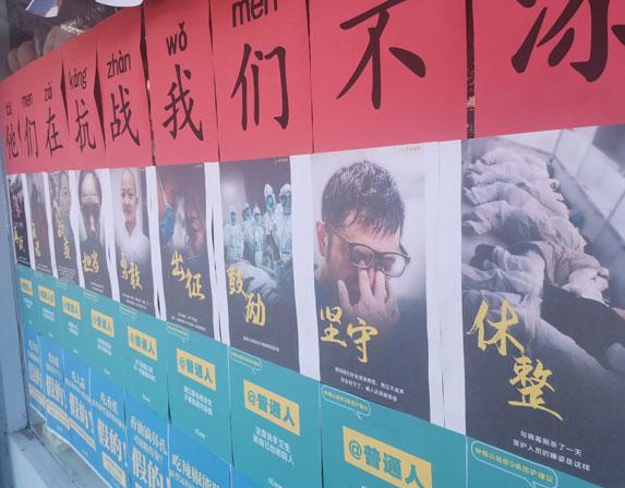 כרזות בסין משבחות את הצוותים הרפואיים וקוראות לאזרחים להישמע להוראות | צילום: kavastudio, Shutterstock