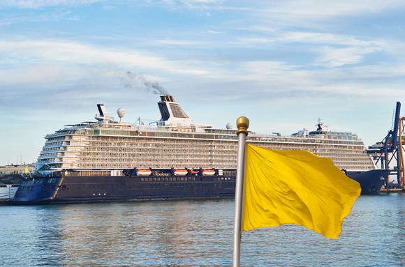 ספינת נופש עוגנת לצד דגל צהוב המזהיר שיש בה חולים | Shutterstock, danielmarin