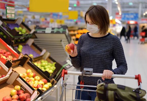 את הפירות והירקות עדיף לקרצף במים זורמים. אישה עם מסכת מגן בקניות במרכול | צילום: Maria Sbytova, Shutterstock