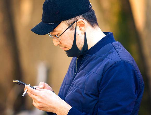 אדם מעשן בזמן שפניו מכוסות במסכה | V.Baturin, Shutterstock
