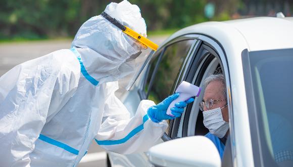 רופאה בבגדי מגן מודדת חום לחשוד בקורונה | צילום: aslysun, Shutterstock