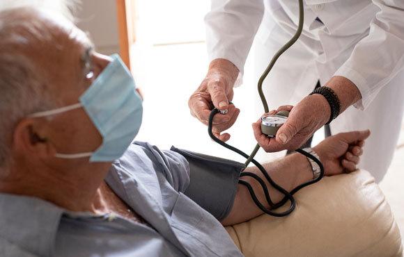 רופא מודד לחץ דם לחולה במסכה | צילום: Alessandro Pintus, Shutterstock