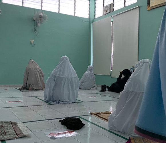 נשים מוסלמיות במלזיה שומרות על ריחוק פיזי בשעת תפילה | צילום: Azura Hanif, Shutterstock