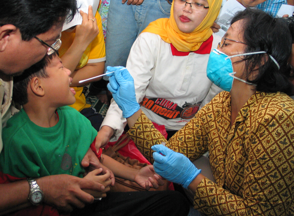 בדיקה לילד באינדונזיה במהלך התפרצות שפעת העופות | צילום: Toto Santiko Budi, Shutterstock