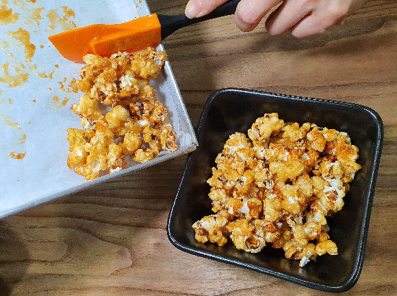 Transferring the baked caramel popcorn from the oven tray to a serving dish | Photo: Toshio Chan, Shutterstock