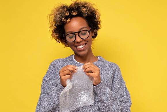 אישה מחייכת כשהיא מפוצצת בועיות בעטיפת פצפצים | Shutterstock, Koldunova Anna