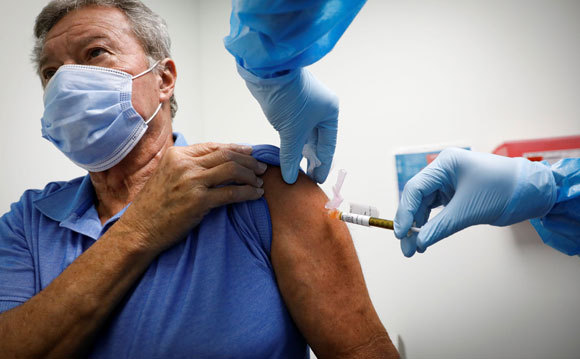 האם אפשר לשלב בין סוגי החיסונים? אזרח בריטי מקבל חיסון בלונדון | צילום: vasilis asvestas, Shutterstock