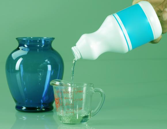 נוזל ניקוי נשפך לכוס מדידה | Shutterstock