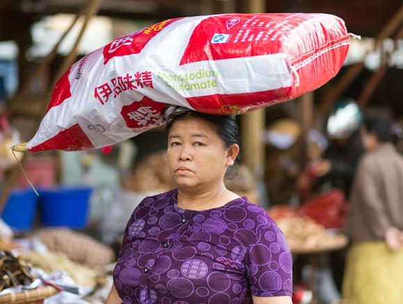 אישה במיאנמר נושאת על ראשה שק גדול של מונוסודיום גלוטמט | צילום: Shutterstock