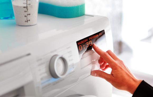 אשה מכוונת את מכונת הכביסה | צילום: ssuaphotos, Shutterstock
