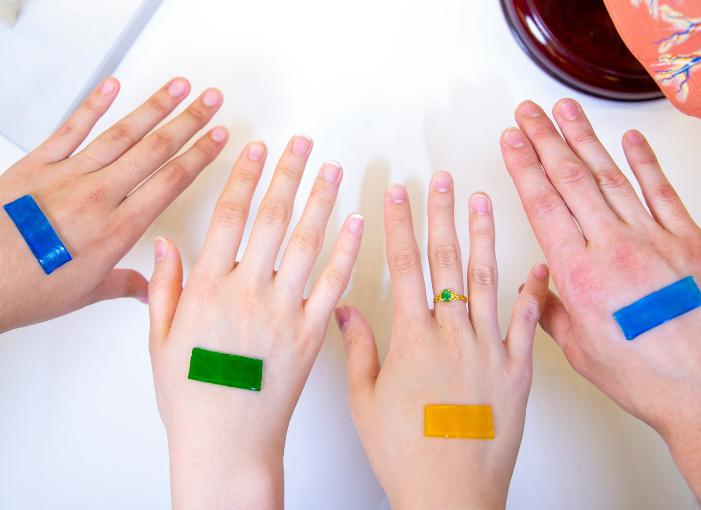 ידיים עם פלסטרים מכל מיני צבעים, מתוך המאמר